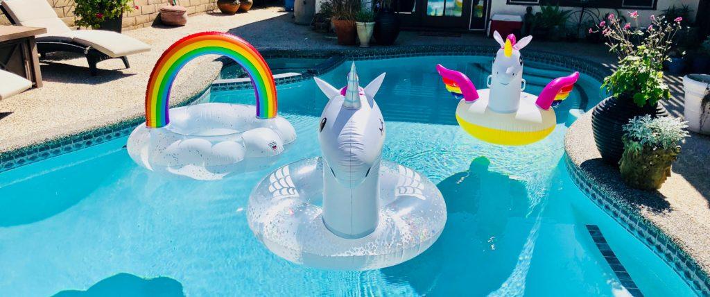 Trois bouées licornes dans une piscine