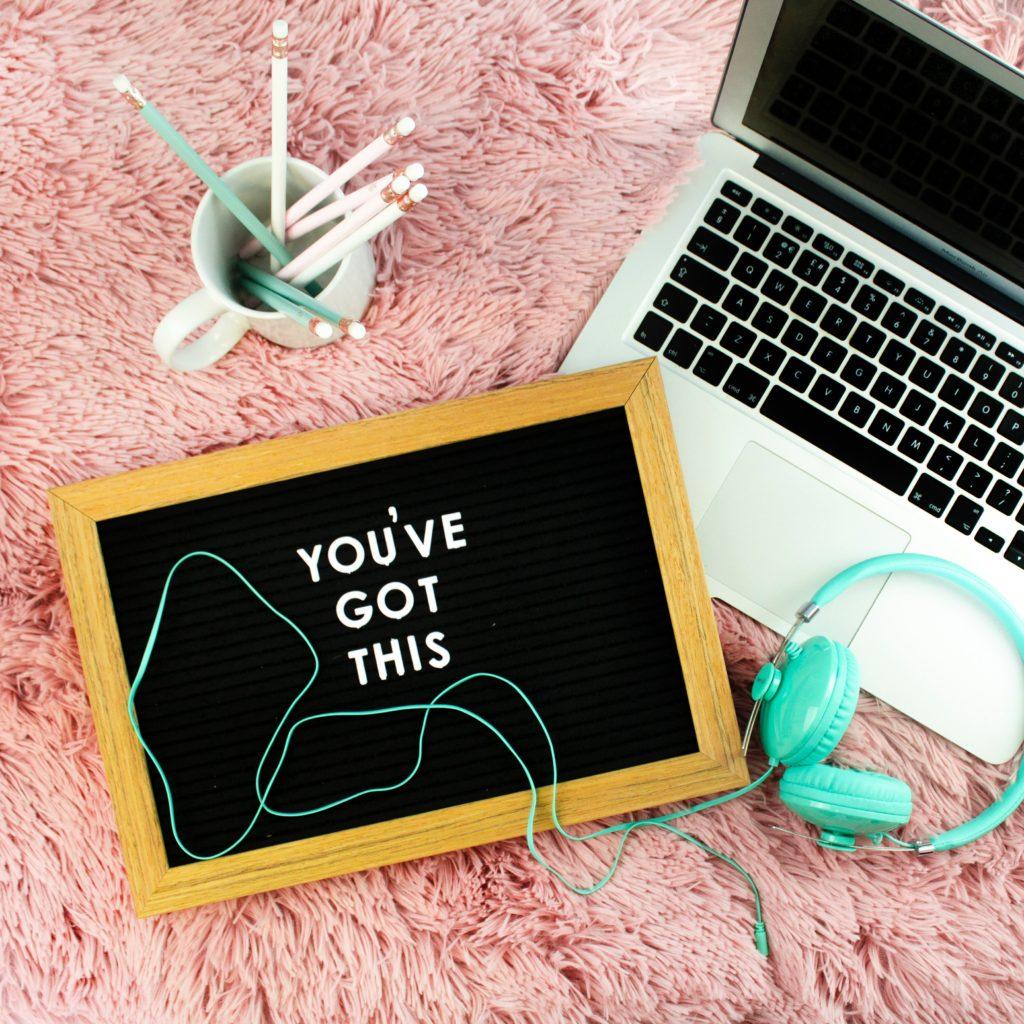 """Ardoise avec écrit """"you've got this"""" sur un plaid rose avec à côté un pot à crayon et un ordinateur portable"""