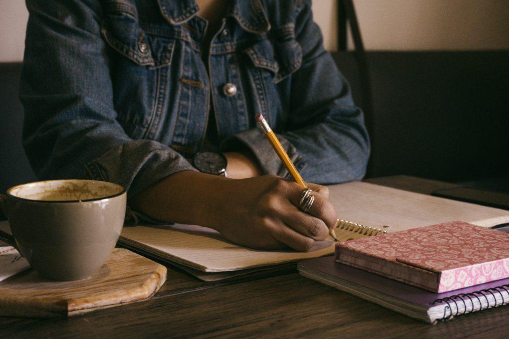 Personne écrivant sur un carnet avec une tasse à côté