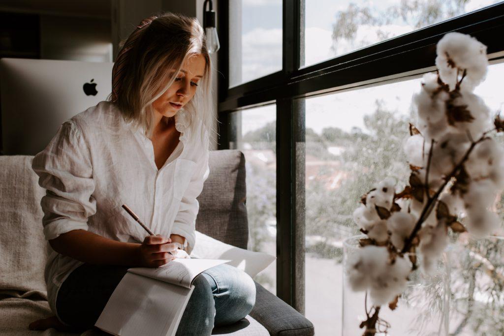 Une femme écrit sur un carnet devant une fenêtre